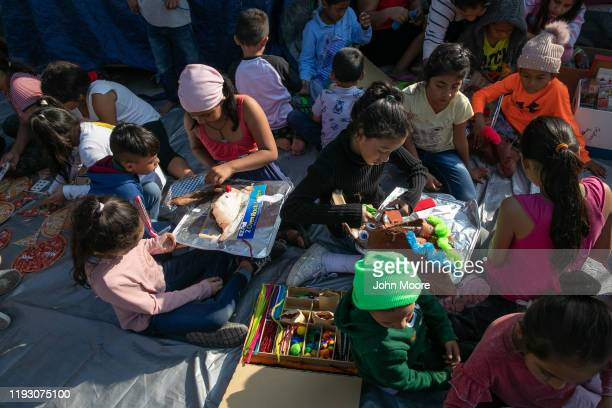 Immigrant children make Christmas decorations during class at The Sidewalk School at a camp for asylum seekers on December 08 2019 in the Mexican...