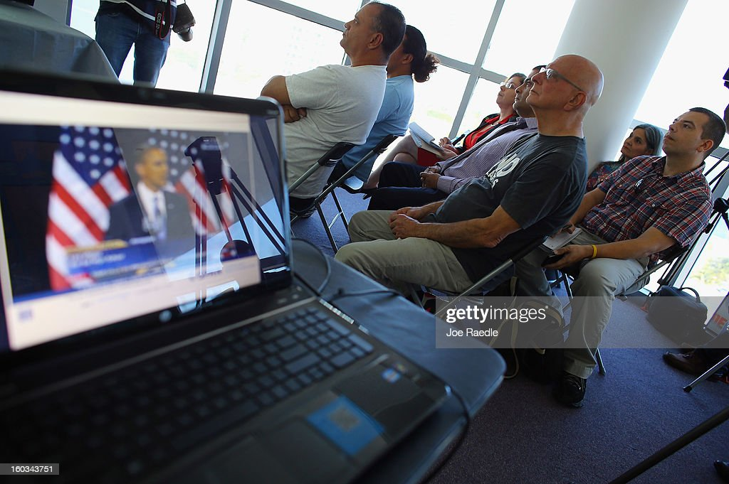 Immigrant families and advocates watch together at the Florida Immigrant Coalition headquarters as President Barack Obama is projected onto a screen from a computer as he makes remarks on immigration policy on January 29, 2013 in Miami, Florida. The President in his speech asked for a comprehensive overhaul of U.S. immigration laws.