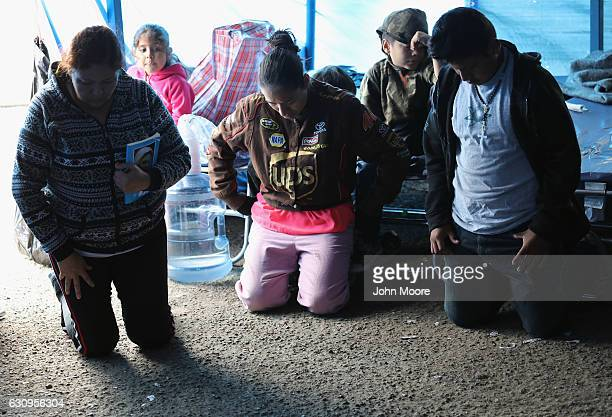 Immigrant families pray at a Catholicrun 'immigrant respite center' before taking a bus from the border into the interior of the United States on...