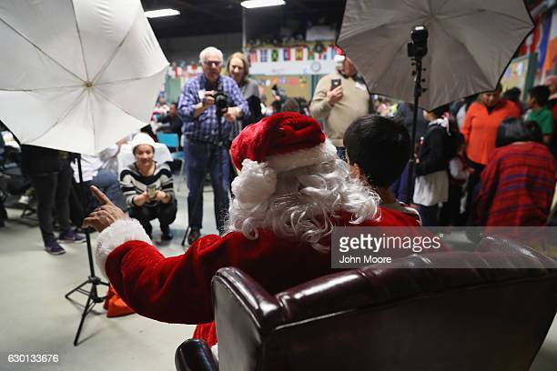 Immigrant family children sitting on Santa's lap pose for photos at a Family Night Christmas party on December 16 2016 in Stamford Connecticut More...