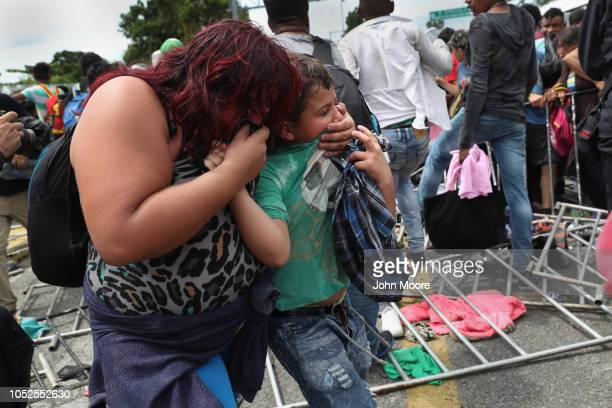 Immigrant family members are overcome with tear gas during a clash between police and the migrant caravan on the border between Mexico and Guatemala...