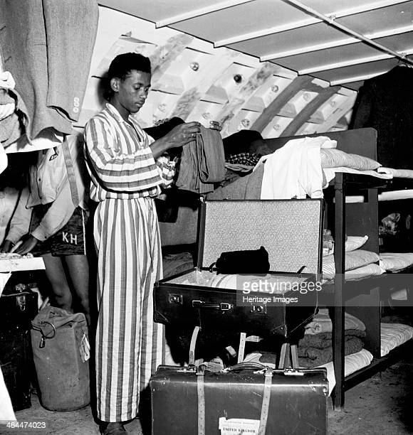 Immigrant living temporarily in a Nissen hut London 1950s Inside a Nissen hut filled with bunk beds a man dressed in pyjamas folds his clothes and...