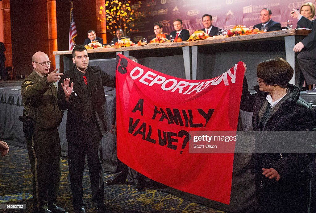 Immigrant rights protestors raise a banner after jumping a security barricade at the Presidential Family forum as Republican presidential candidates (L to R) Ted Cruz (R-TX), Ben Carson, Sen. Marco Rubio (R-FL), Sen. Rand Paul (R_KY), Rick Santorum, Mike Huckabee, and Carly Fiorina watch on November 20, 2015 in Des Moines, Iowa. Attendance at the event was lower than organizers had hoped as an early-winter snowstorm moved through the area dumping several inches of snow on the city.