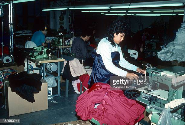 Immigrant workers at a sweatshop in Queens New York are photographed March 25 1990 Employees work long hours for very little pay and are exposed to...
