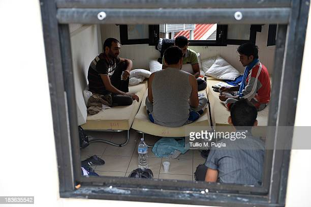 Immigrants are detained after their arrival in the temporary shelter Center on October 8 2013 in Lampedusa Italy The search for bodies continues off...