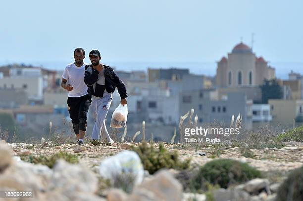 Immigrants are seen outside of the temporary shelter Center where they are detained after their arrival at the island on October 4 2013 in Lampedusa...