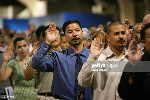 Immigrants are sworn in as US citizens during naturalization ceremonies on July 26 2007 in Pomona California The 6000 people taking their citizenship...