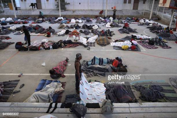 Immigrants begin to awake after a night's rest on an outdoor basketball court during a pause on their journey towards the USMexico border on April 22...