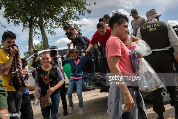 Immigrants climb down from a pickup after being taken into custody by US federal agents on July 02 2019 in Los Ebanos Texas Hundreds of immigrants...