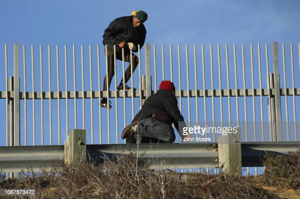 Immigrants climb over a secondary fence after climbing over the main USMexico border fence on December 2 2018 from Tijuana Mexico Numerous members of...