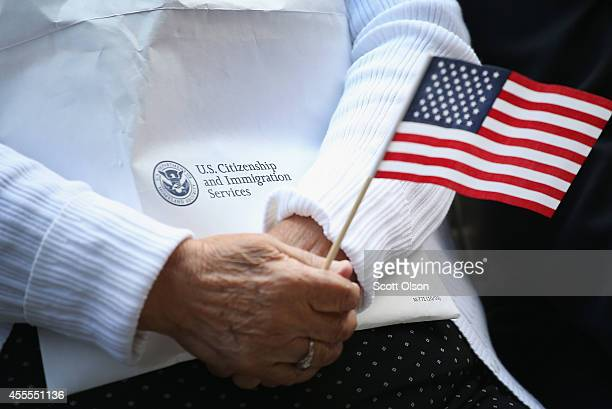 Immigrants from 25 countries participate in a naturalization ceremony in Daley Plaza on September 16, 2014 in Chicago, Illinois. Seventy people were...