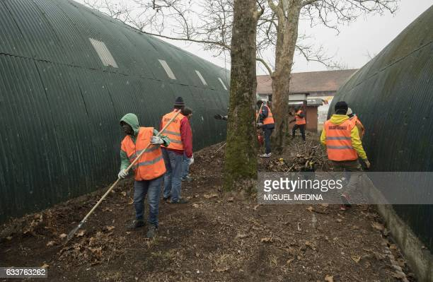 VELASQUEZ Immigrants from Mali Ivory Coast Niger Nigeria Pakistan Camerun are pictured cleaning a disused military base in Belluno northern Italy on...