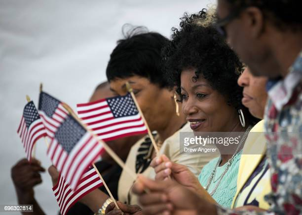 Immigrants hold American flags as they take part in a naturalization ceremony outside of the Wyckoff Farmhouse Museum June 15 2017 in the Brooklyn...