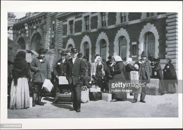 US Immigrants Immigrants stand with trunks outdoors in front of a building on Ellis Island New York City Ellis Island New York City