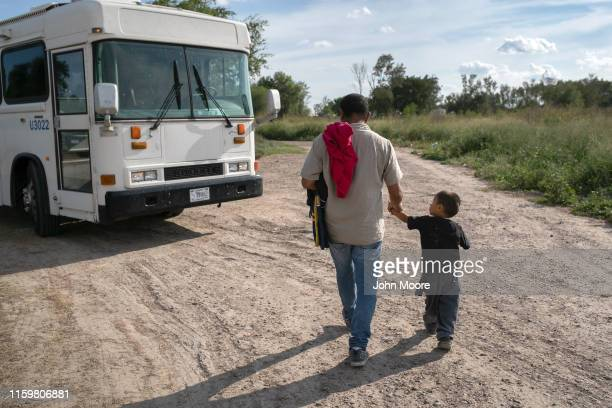 Immigrants including a 3 1/2 year old unaccompanied minor from Honduras wait to be bussed to a US Border Patrol facility in McAllen after crossing...