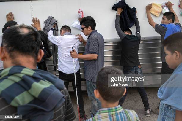 Immigrants including a blind man from El Salvador wait to be searched and then bussed to US Border Patrol facility in McAllen after crossing the...