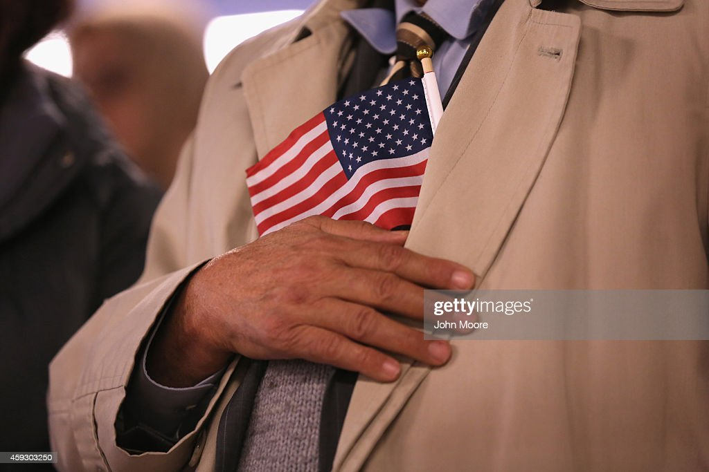 Immigrants listen to the U.S. National Anthem at a naturalization ceremony on November 20, 2014 in Newark, New Jersey. Sixty immigrants from 25 countries became American citizens during the ceremony at the U.S. Immigration and Citizenship Services (USCIS) office at Newark's Federal Building.