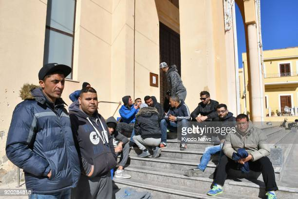 Immigrants mainly from Tunisia gather in front of a church on Feb 7 2018 on the Italian island of Lampedusa a primary European entry point for...