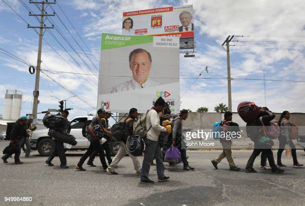 Immigrants most of them from Central America pass by Mexican presidential campaign billboards after traveling by freight train on their journey...