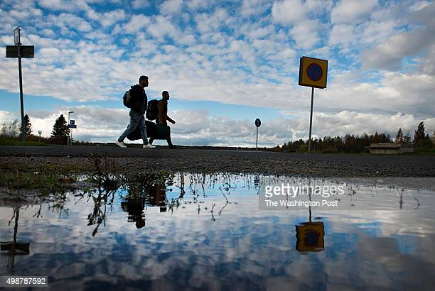 Immigrants mostly from Iraq walk from a bus station in Sweden to Finland to a makeshift customs checkpoint in the northern border in Tornio Finland...