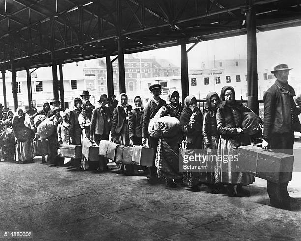 Immigrants on line leaving Ellis Island waiting for ferry to NY Photo ca 1900 Undated photograph