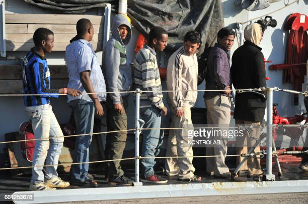 Immigrants part of a group of more than 180 people wait after they disembarked from the Italian Military ship Fenice in the port of Crotone southern...