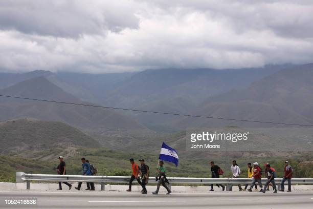 Immigrants part of a migrant caravan carry a Honduran flag on their journey on October 17 2018 in Guastatoya Guatemala The caravan of thousands of...