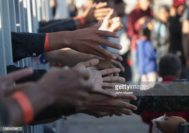 Immigrants reach for food handouts at a temporary migrant shelter set up near the USMexico border on November 18 2018 in Tijuana Mexico Parts of the...
