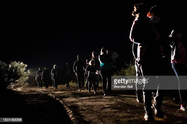 Immigrants seeking asylum walk to be processed at a border patrol processing facility after crossing the Rio Grande into the United States on June...