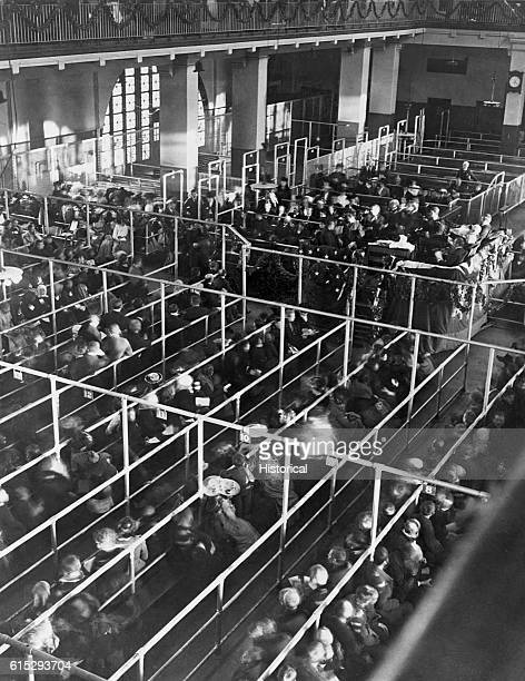 Immigrants sit and wait on long numbered benches to be processed for entry into the United States. Officials sit on a raised platform which is...