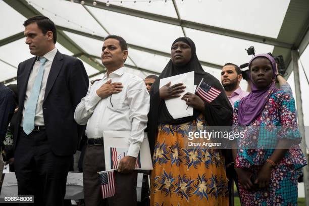 Immigrants stand for the National Anthem during a naturalization ceremony at Franklin D Roosevelt Four Freedoms Park on Roosevelt Island June 16 2017...