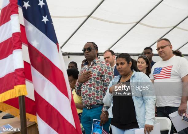 Immigrants stand for the US national anthem at a naturalization ceremony outside of the Wyckoff Farmhouse Museum June 15 2017 in the Brooklyn borough...