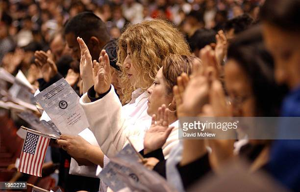 Immigrants take the US citizenship oath along with more than 4000 others at a naturalization ceremony April 25 2003 in Los Angeles California...