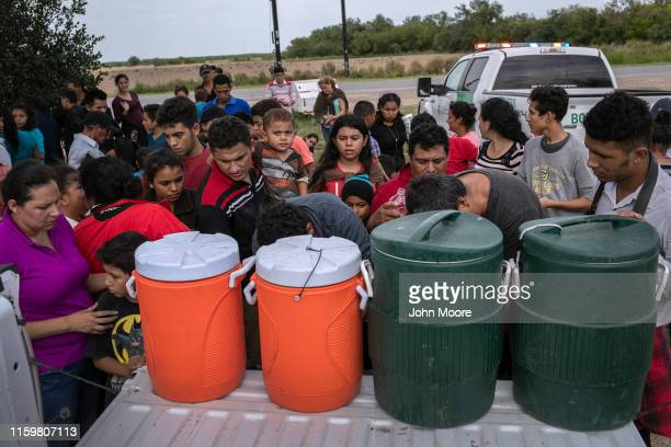 Immigrants take water from the back of a US Border Patrol pickup on July 02 2019 in Los Ebanos Texas Hundreds of immigrants most from Central America...