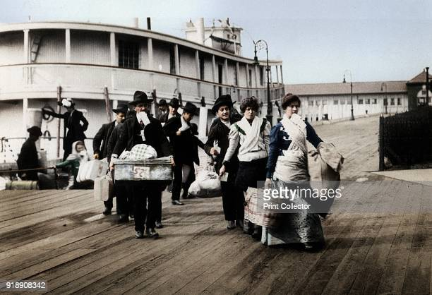 Immigrants to the USA landing at Ellis Island, New York, c1900. They head for the processing centre, each carrying a paper with an entry number which...