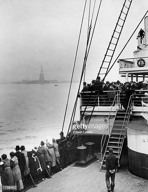 Immigrants view the Statue of Liberty while entering New York harbor aboard an ocean liner en route to Ellis Island New York City 1910s