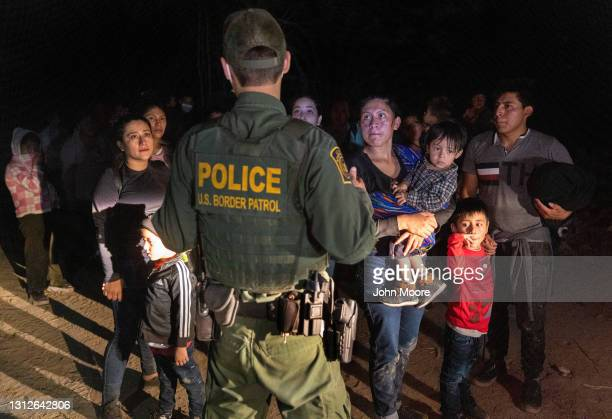 Immigrants wait for a U.S. Border Patrol agent to lead them up from the bank of the Rio Grande after they crossed the U.S.-Mexico border on April 14,...