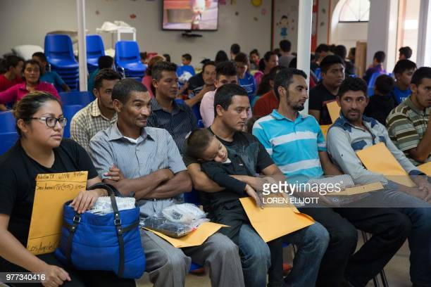 Immigrants wait for assistance with travel plans after being released from detention through the catch and release immigration policy at a Catholic...