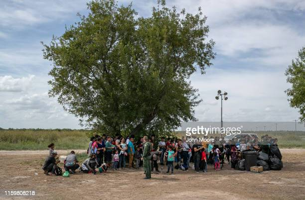 Immigrants wait in the shade after they were taken into custody by US Border Patrol agents on July 02 2019 in Los Ebanos Texas Hundreds of immigrants...