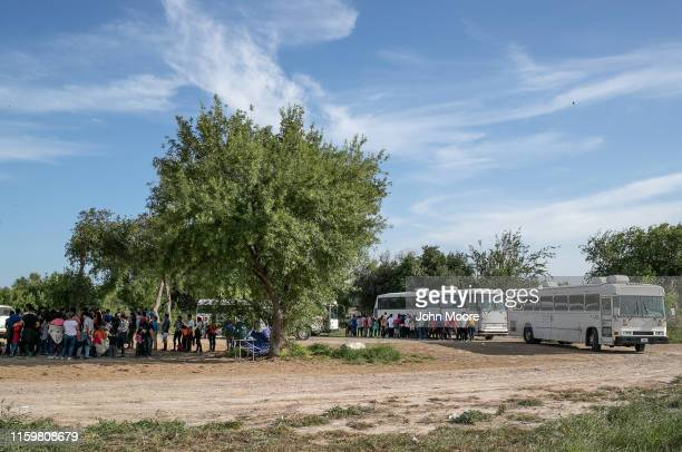 Immigrants wait to be bussed to US Border Patrol facility in McAllen after crossing the Rio Grande from Mexico on July 02 2019 to Los Ebanos Texas...