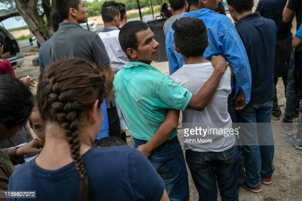 Immigrants wait to be interviewed by US Border Patrol agents after they were taken into custody on July 02 2019 in Los Ebanos Texas Hundreds of...