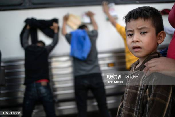 Immigrants wait to be searched and then bussed to US Border Patrol facility in McAllen after crossing the border from Mexico on July 02 2019 in Los...