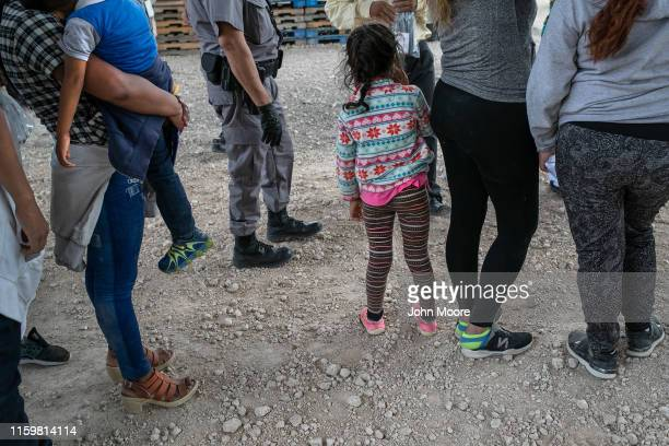 Immigrants wait to be transported to a processing center after they were taken into custody by US Border Patrol agents on July 02 2019 in McAllen...