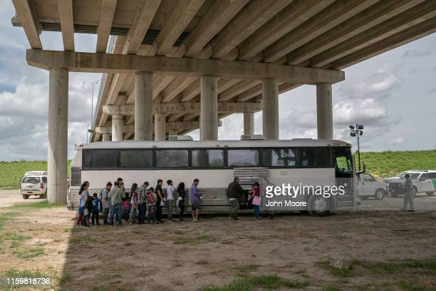 Immigrants wait to be transported to a US Border Patrol processing center after they were taken into custody on July 02 2019 in McAllen Texas The...