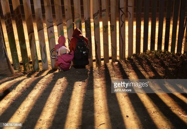 Immigrants wait to climb over the USMexico border fence on December 2 2018 from Tijuana Mexico Numerous members of the caravan were able to cross...