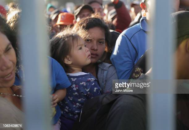 Immigrants wait to eat at a temporary migrant shelter set up near the USMexico border on November 18 2018 in Tijuana Mexico Parts of the migrant...