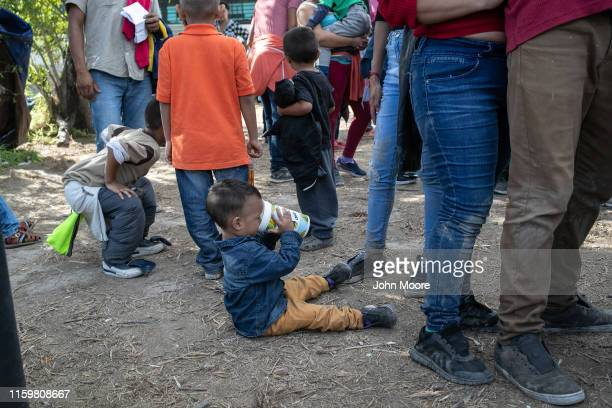 Immigrants wait to speak with US Border Patrol agents before being transferred to the McAllen Border Patrol facility on July 02 2019 in Los Ebanos...