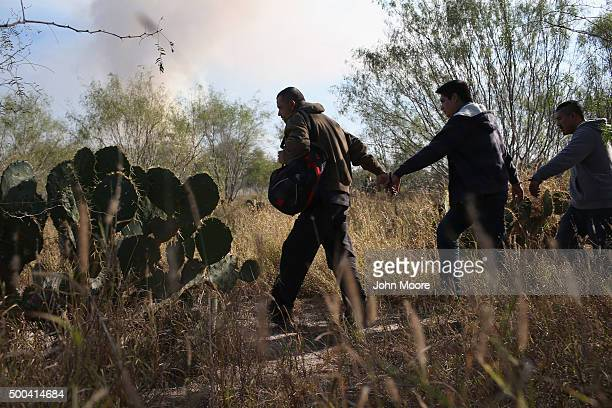Immigrants walk handcuffed after illegally crossing the USMexico border and being caught by the US Border Patrol on December 7 2015 near Rio Grande...
