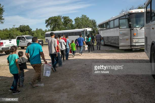 Immigrants walk to US Homeland Security busses to be transferred to a US Border Patrol facility in McAllen after crossing from Mexico on July 02 2019...