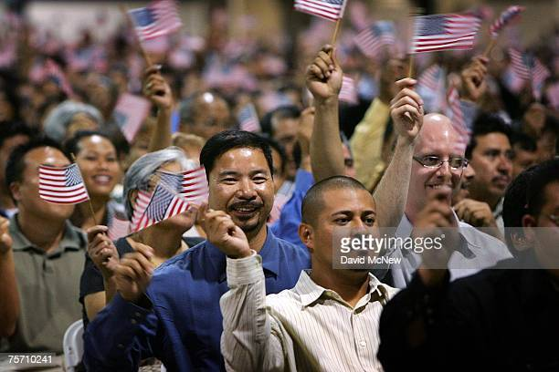Immigrants wave flags after being sworn in as U.S. Citizens in naturalization ceremonies on July 26, 2007 in Pomona, California. Some of the 6,000...